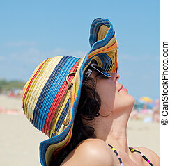 Woman with hat enjoying on beach
