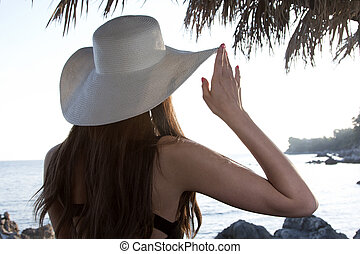 Woman with hat looking at sea