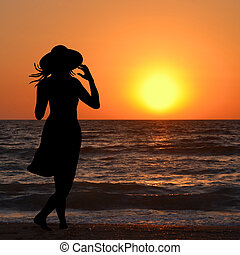 Woman with hat looking at sunrise