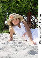 Woman with hat lying on white sand