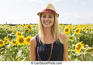 Woman with hat on sunflowers field at sunset
