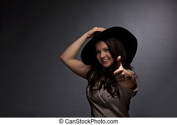 woman with hat posing thumbs up