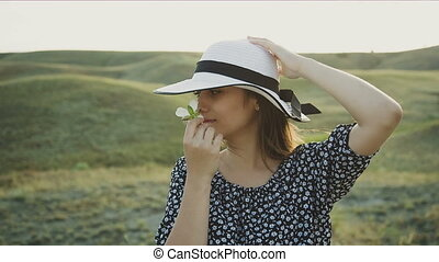 Woman With Hat Smelling a Flower