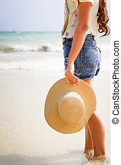 woman with hat standing on the beach