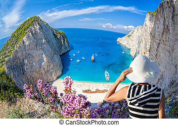 Woman with hat watching Navagio beach with shipwreck on Zakynthos island in Greece