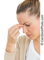 Woman with headache pinching her nose and wincing