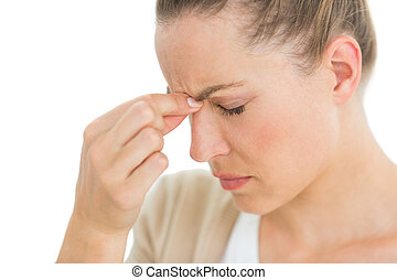 Woman with headache pinching her nose