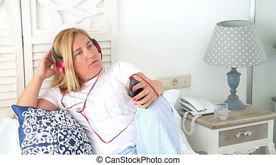 Woman with headphone laying on a bed