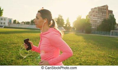 Young woman with headphones and smartphone runs through the stadium at sunset
