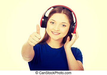 Woman with headphones and thumbs up.