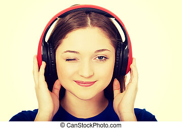 Woman with headphones blinks eye.