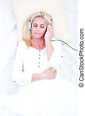 Woman with headphones in Bed
