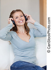 Woman with headphones on the sofa listening to music