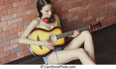Woman with headphones playing guitar - Lovely young female...
