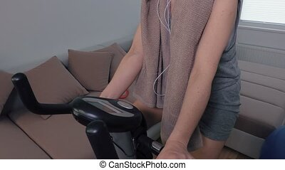 Woman with headphones riding exercise bike