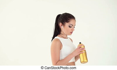 woman with headphones running and drinking water