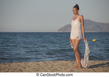 woman with headscarf on the beach