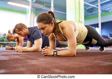 woman with heart-rate tracker exercising in gym
