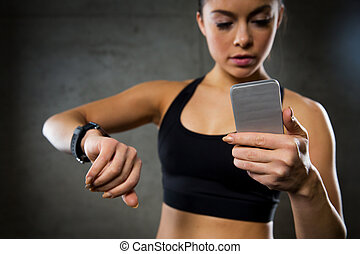 woman with heart-rate watch and smartphone in gym - sport, ...
