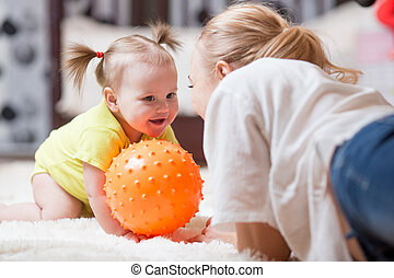 woman with her baby playing with a ball, while they are lying on plush carpet in the living room