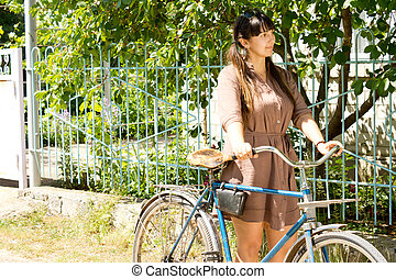 Woman with her bike outside a country home