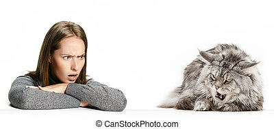 Woman with her cat over white background - The angry and ...