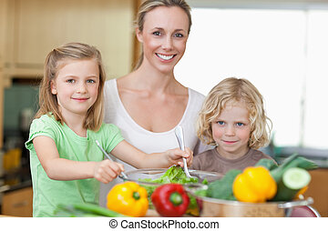 Woman with her children preparing salad