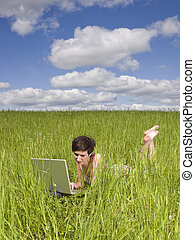 Woman with her computer in the grass