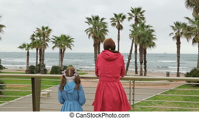 Woman with her daughter admire beautiful seascape