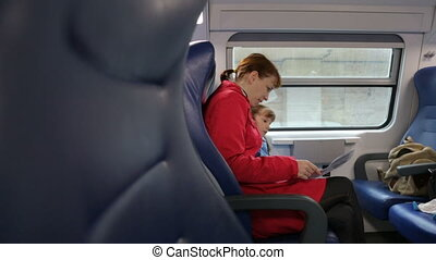 Woman with her daughter in train