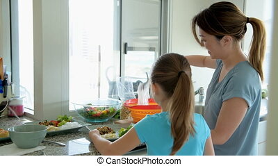 Woman with her daughter keeping noddle on plate in kitchen...