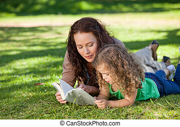 Woman with her daughter reading a b