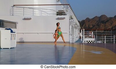 woman with her daughter runs in ship - happy young woman...