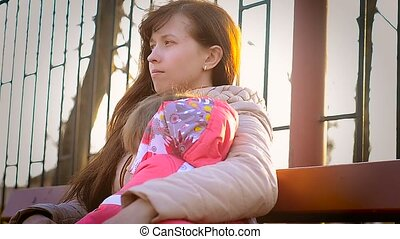 Woman with her daughter sitting on the bench