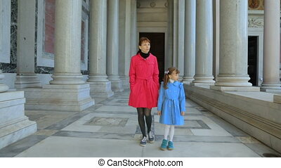 Woman with her daughter walking along the columns in Basilica of Saint Paul