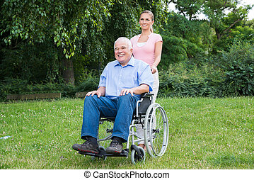 Woman With Her Disabled Father On Wheelchair
