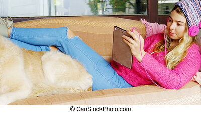 Woman with her dog listening music on sofa 4k - Woman with...