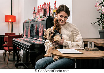 Woman with her dog sitting in the cafe