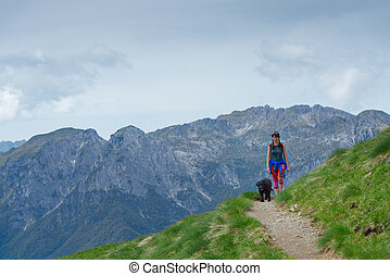 Woman with her dog walking on the mountain path