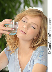 Woman with her eyes closed holding a glass of water