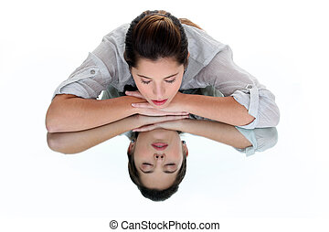 Woman with her eyes closed leaning on a mirrored table