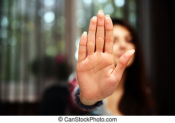 Woman with her hand extended signaling to stop (only her...