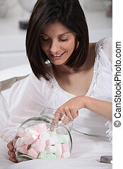 Woman with her hand in the marshmallow jar