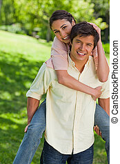 Woman with her hand on her friends head as he is carrying her