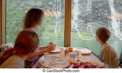 Woman with her kids sit at table and eat in front of window