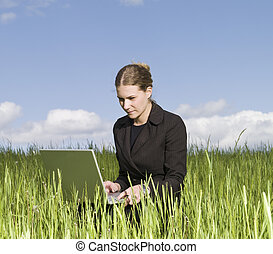 Woman with her laptop in the grass