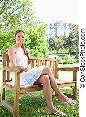 Young woman with her legs crossed sitting on a park bench