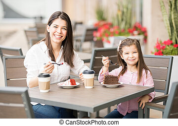 Woman with her little daughter having cake