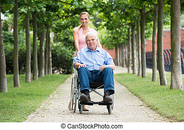 Woman With Her Old Senior Father On Wheelchair