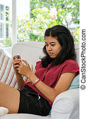 Woman with her smart phone sitting on sofa in living room